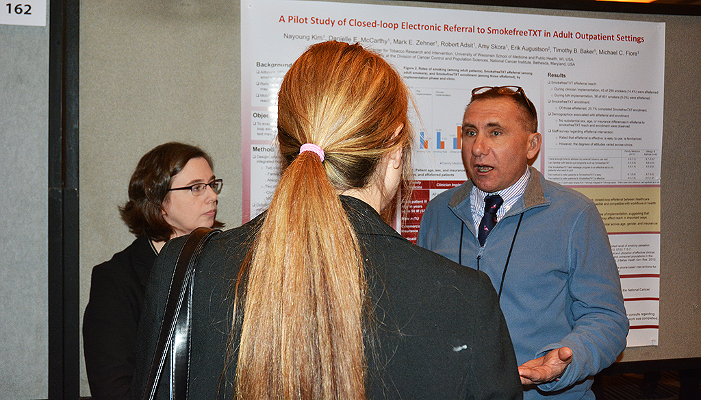 Mark Zehner (right) and UW-CTRI Associate Director of Research Dr. Danielle McCarthy (left) discuss their research with a fellow SRNT attendee.